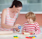 Smiling boy with his mother and cookie cutter — Stock Photo