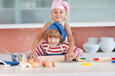 Blond girl baking with her little brother — Stock Photo