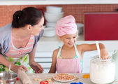 Merry little girl baking with her mother cookies — Stock Photo