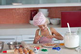 Blond girl baking biscuits for her family — Stock Photo