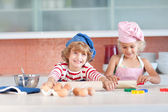 Jolly siblings cooking biscuits — Stock Photo