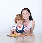 Moeder en zoon thuis schrijven — Stockfoto