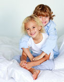 Little girl and boy on the bed — Stock Photo