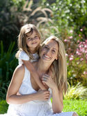 Beautiful mother and daughter outdoors in the sunshine — Stock Photo