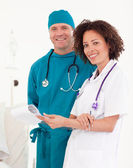 Friendly nurse with handsome surgeon in blue scrubs — Stock Photo