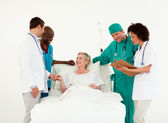 Elderly smiling patient between a medical team — Stock Photo