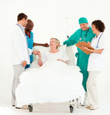 Surgeon with doctors looking after a senior patient — Stock Photo
