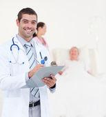 Successful male doctor writing on clip board — Foto Stock