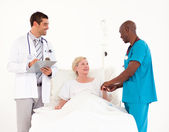 Team of doctors with a patient — Stock Photo