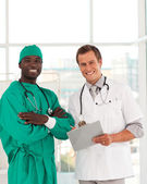 Surgeon and doctor smiling at camera — Stock Photo