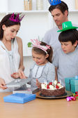 Cute girl unpacking Birthday presents with her family — Stock Photo