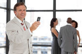 Charismatic businessman holding a phone at workplace with his co — Stock Photo