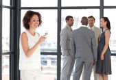 Businesswoman holding a phone at workplace with his colleagues — Stock Photo