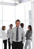 Young business manager standing at the camera with his team — Stock Photo