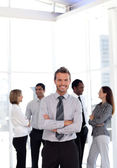 Charming business manager standing at the camera with his team — Stock Photo