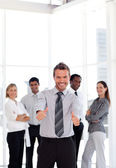 Positive business manager standing at the camera with his team — Stock Photo