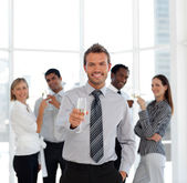 Smiling business manager holding a glass with his team — Stock Photo