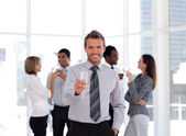 Happy business manager holding a glass with his team — Stock Photo