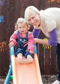 Cute girl and her mother having fun with a chute — Stock Photo