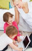 Linda familia divirtiéndose con un ordenador portátil en la sala de estar — Foto de Stock