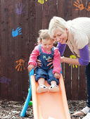 Smiling girl and her mother having fun with a chute — Stock Photo