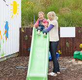 Caucasian girl and her mother having fun with a chute — Stock Photo