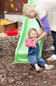 Little girl and her blond mother having fun with a chute — Stock Photo