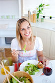 Positive young woman eating a salad — Stock Photo