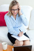 Angry businesswoman sitting on a sofa — Stock Photo
