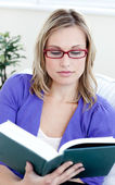 Young woman with glasses reading a book — Stock Photo