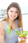 Smilling woman eating salad in the kitchen — Stock Photo