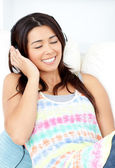 Radiant young woman sitting on sofa and listening music — Stock Photo