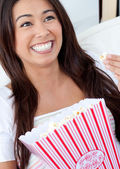 Woman sitting on sofa and eating popcorn — ストック写真