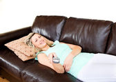 Slack woman lies on sofa and watches TV — Stock Photo