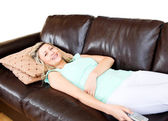 Unstressed woman lies on sofa and watches TV — Stock Photo