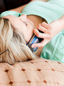Unwind woman lies on sofa and phoning — Stock Photo