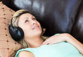 Young woman lies on a sofa and listen music — Stock Photo