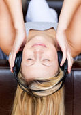 Sleeping woman lies on a sofa and listen music — Stock Photo