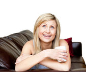 Laughing woman lies on a brown sofa — Stock Photo