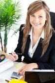 Smilling businesswoman working in her office with a calculator — Stock Photo