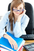 Smilling female doctor with glasses sitting in office — Stock Photo