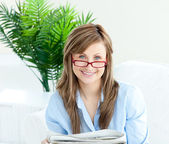 Glowing woman with glasses reading newspaper — Stock Photo