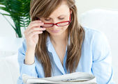Enthusiastic woman with glasses reading a newspaper — Stock Photo