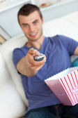 Smiling man is relaxing in the living-room with popcorn — Stock Photo