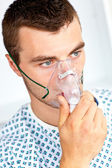 Serious male patient with a mask looking to the side — Stock Photo
