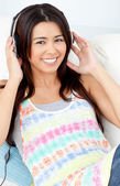 Jolly woman with headphones on lying on a sofa — Stock Photo