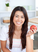 Beautiful woman eating an apple smiling at the camera — Stock Photo