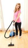 Smiling woman use vacuum cleaner — Стоковое фото