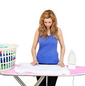 Concentrated woman behind an ironing board — Stock Photo