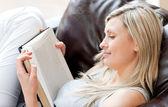 Uroczą kobietą, czytanie książki, siedząc na kanapie — Zdjęcie stockowe